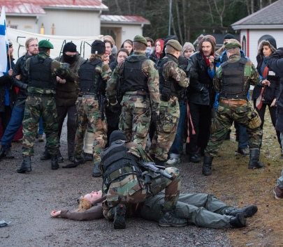 Uralian Defense Force soldier with heavily wounded protester. Ingame. Photo: Tuomas Puikkonen (CC-BY 2.0)